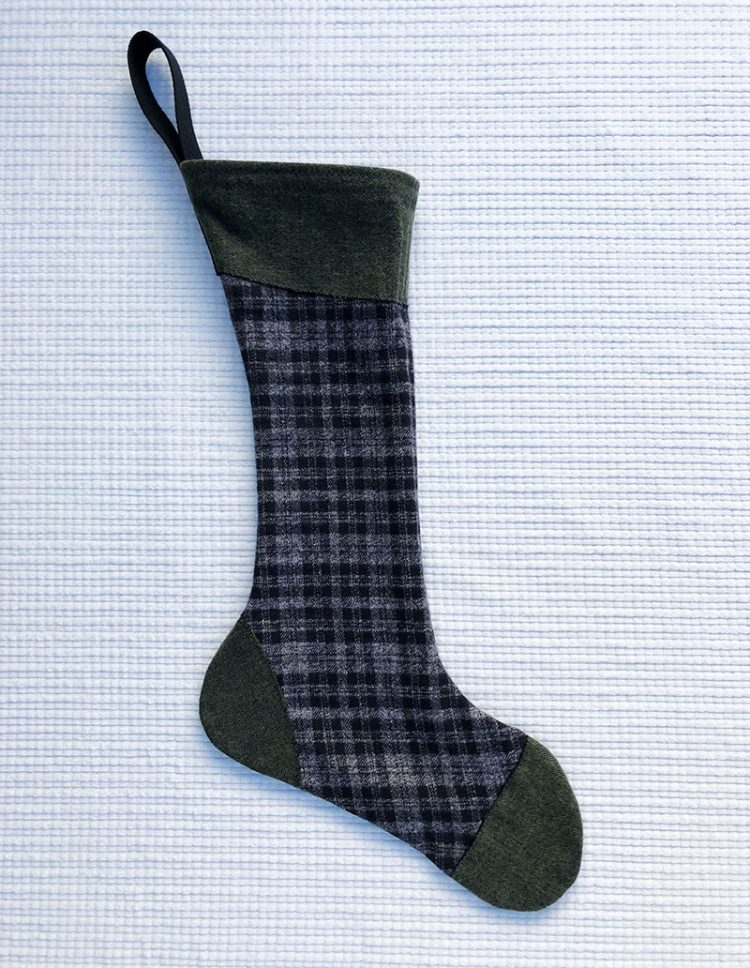 100% cotton flannel stocking with black and gray plaid body and green accents at cuff, toe and heel